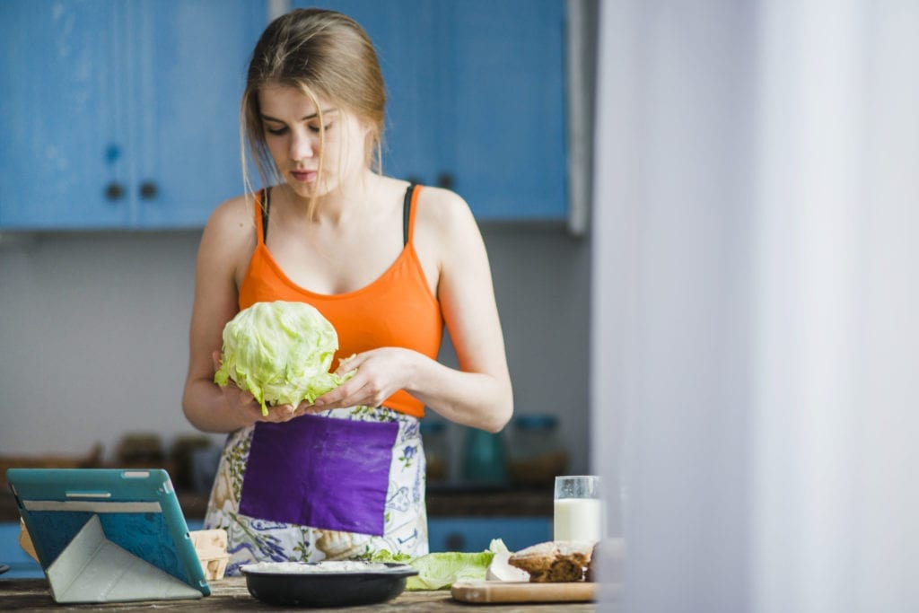 Woman holding fresh cabbage for preparation of sauerkraut at home.