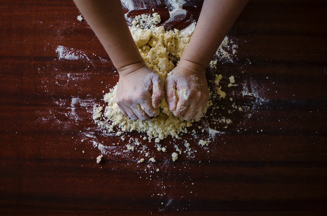 A pair of hands kneading dough for making seitan or wheat gluten