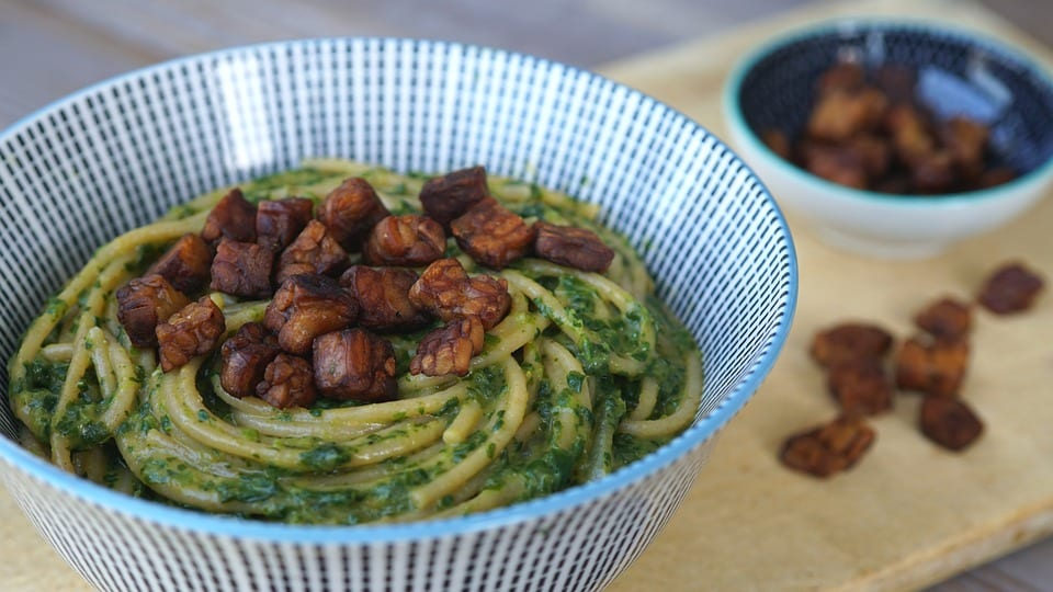 Vegan tempeh spinach spaghetti in a bowl with tempeh chips on the side.