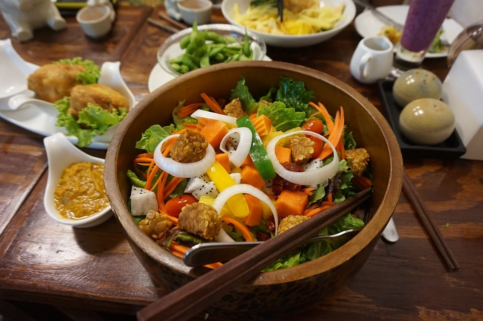 Tempeh salad in a wooden bowl with chopsticks alongside other foods