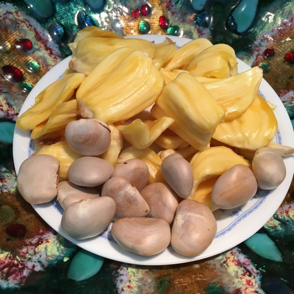 Jackfruit seeds and flesh in a white plate.
