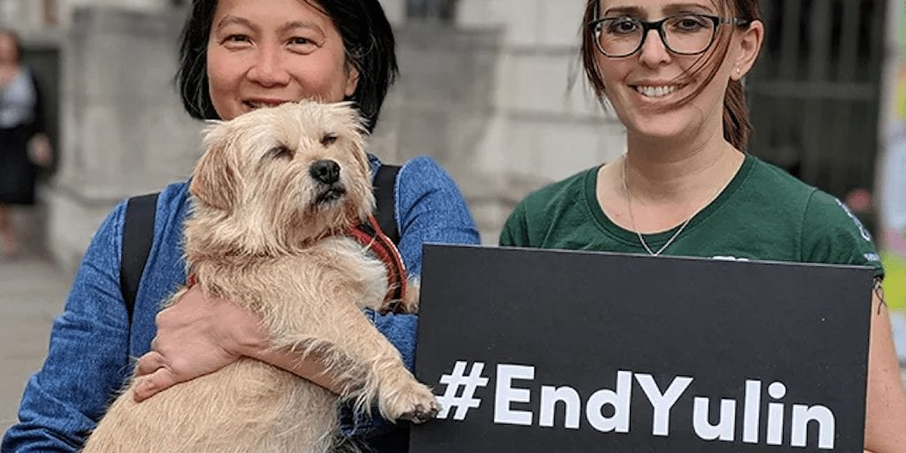 two girls holding a dog and banner against Yulin festival