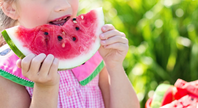 Kid eating watermelon showing Veganism is on the rise among UK schoolkids